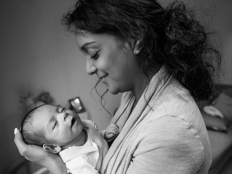 Mum holding her newborn babyand smiling-naturalfamilyphotography-Bucks wedding photography _