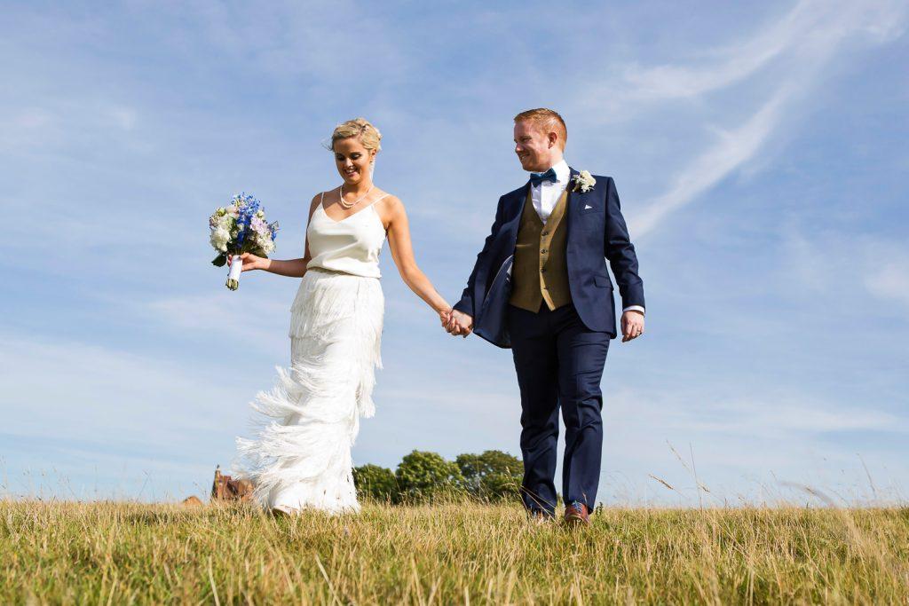 bride and groom holding hands Blue sky Dodford Manor_